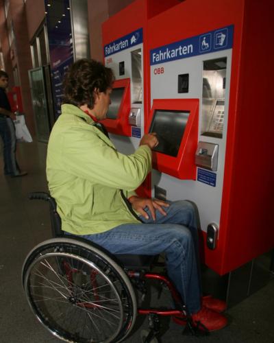 Bild von einer Rollstuhlfahrerin die problemlos am Automaten ein Ticket kauft