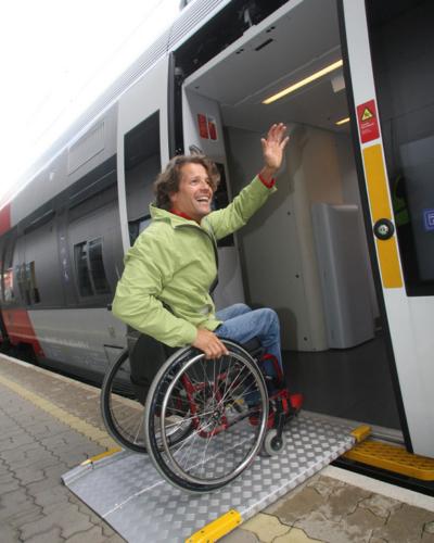 Foto von einem Rollstuhlfahrer der gerade barrierefrei in einen Zug einsteigt
