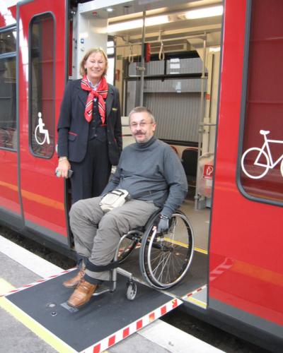 Foto von einem Rollstuhlfahrer der gerade barrierefrei aus einem Zug austeigt