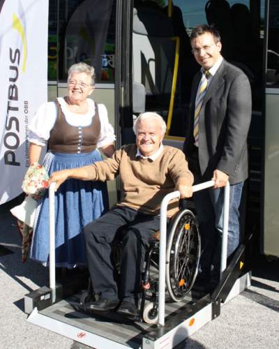 Foto von einem Rollstuhlfahrer der barrierefrei aus einem Postbus aussteigt