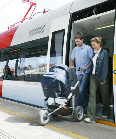 Ein Pärchen mit Kinderwagen steigt aus einem Zug mit ebenen Einstieg aus