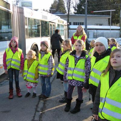 Eine Kindergruppe in Warnwesten steht vor einem Stadtbus