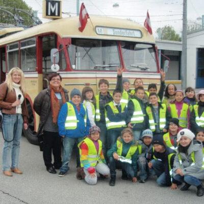 Foto von einer Schulklasse vor einem alten Bus