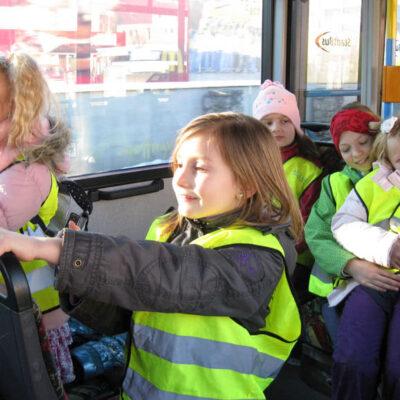 Fünf Kinder in Warnwesten sitzen in einem Bus
