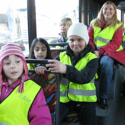 Eine Gruppe von Kinder in Warnwesten sitzen in einem Bus