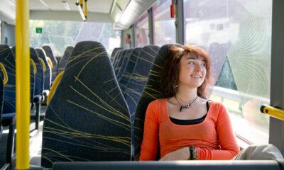 Bild von einer jungen Frau die in einem Bus sitzt und lächelnd aus dem Fenster schaut
