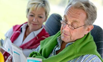 Bild von einem älteren Pärchen, das im Bus sitzt und eine Broschüre liest