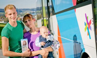 Bild von einem jungen Pärchen, die mit ihrem Baby auf dem Arm vor einem Bus stehen